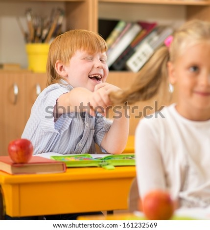 Little redhead schoolboy holding girl's plait during lesson  - stock photo