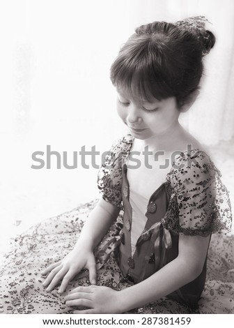 Little redheaded girl wearing green trimmed costume of ballet dancer for a performance, sitting on the floor and daydreaming looking downwards, selective focus, sepia tone - stock photo