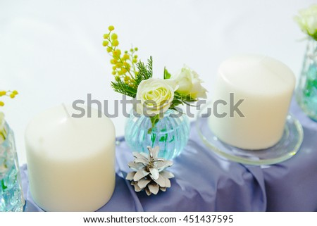 Little roses in a round glass vase standing between thick white candles - stock photo