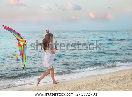 Little running girl with flying kite on beach at sunset - stock photo