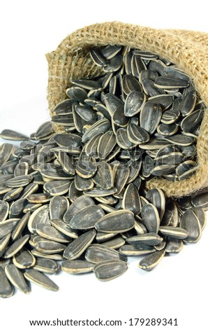 Little sack of dried sunflower seeds (Helianthus annuus L.) on white background.