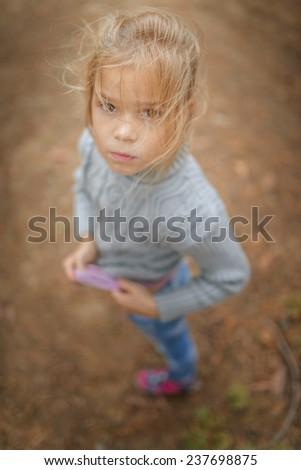 Little sad beautiful girl in sweater in autumn city park. - stock photo