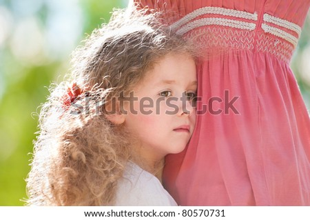 Little sad daughter hugging her mother. Nature background. - stock photo