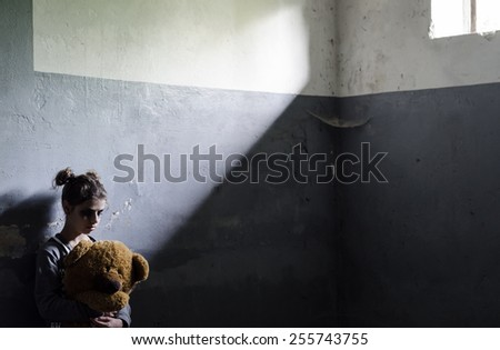 Little sad girl hiding or locked in the basement. - stock photo