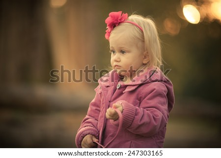 Little sad girl in the park. Pink flower in her hair. Pink coat. Art blurry background. Natural light. Sunset.
