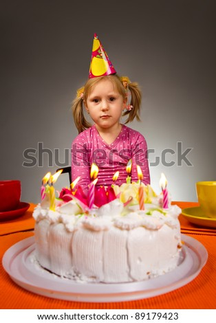 Little sad girl sitting in front of birthday cake - stock photo