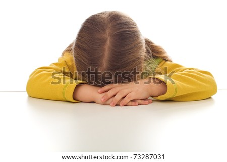 Little sad girl sulking or crying at the table - isolated - stock photo