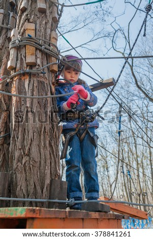 Little sad girl using carbine in rope park challenge. Girl is afraid. Spring weather. Selective focus on girls head.