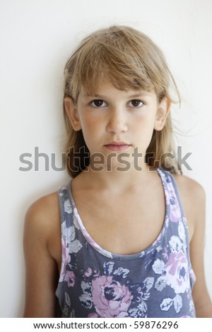 little sad girl with brown eyes standing nearby white wall - stock photo