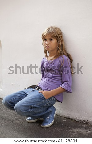 little sad girl with long hair wearing jeans - stock photo