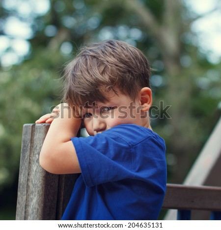 Little sad kid on playground, outdoor portrait - stock photo