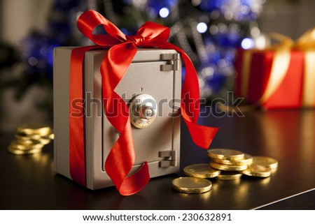 Little safe with red ribbon and golden coins - stock photo