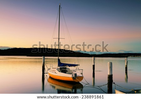 Little sailing boat or yacht tied to its moorings at sunrise, the soft light reflected in the serene water. - stock photo