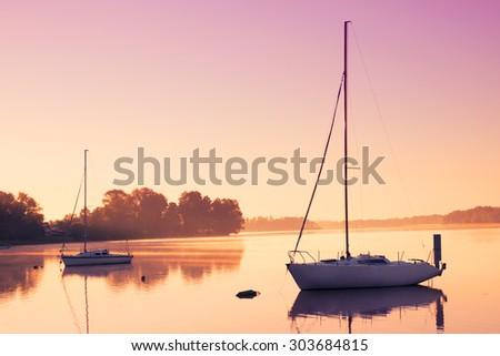 Little sailing boats reflect in  the serene water during sunrise. - stock photo