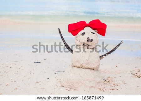 Little sandy snowman with bow on white Caribbean beach - stock photo
