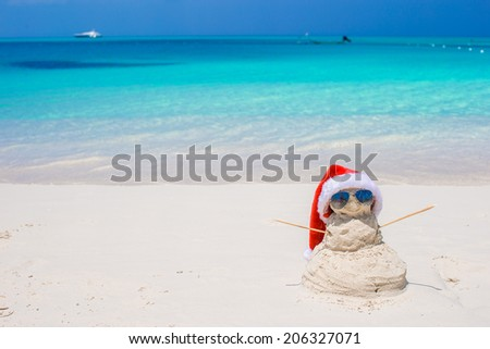 Little sandy snowman with red Santa Hat on white Caribbean beach - stock photo