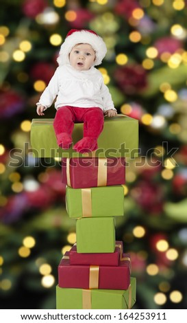little santa baby with christmas hat seated on a big stack of gifts
