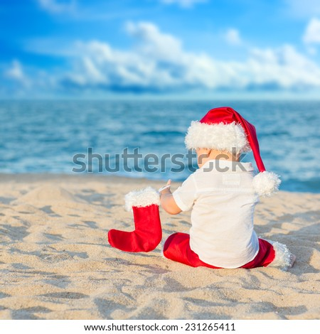 Little Santa boy on the beach. - stock photo