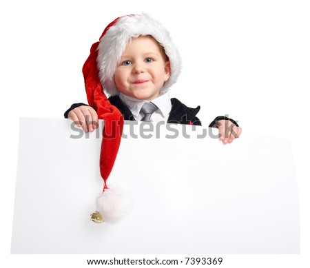 Little Santa helper with banner. Cute playful boy in Santa hat holds white banner.