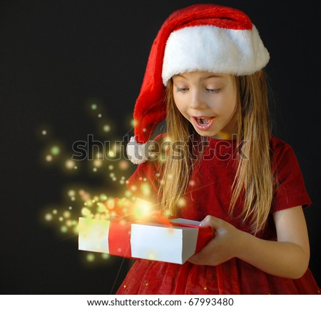 Little santa holding a gift she is very surprised - stock photo