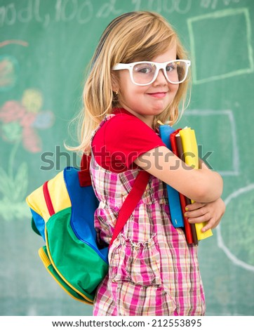 Little school blonde girl in school classroom with backpack and books posing - stock photo