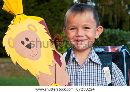 Little school boy with his blue schoolbag and a large cornet of cardboard filled with sweets and little presents given to children on their first day at school. - stock photo