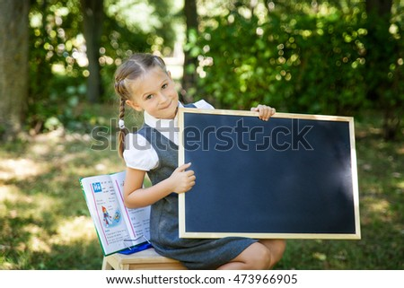 Little school girl in a uniform with a chalkboard. Back to school outdoors. Place for text
