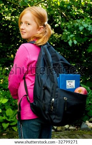 Little school girl is going back to school - stock photo