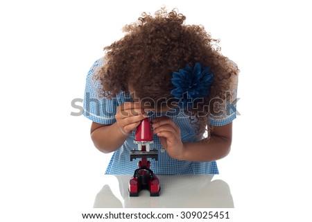 Little school girl looking through a microscope. - stock photo