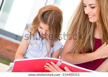 Little school girl showing sketchbook to her mother