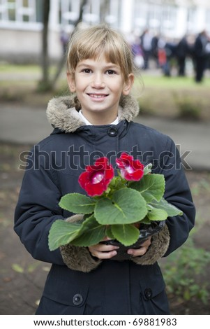 Little school girl with her flower for teacher  on their first day at school. - stock photo