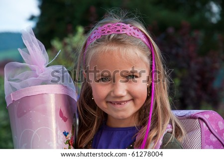 Little school girl with her pink schoolbag and a large cornet of cardboard filled with sweets and little presents given to children  on their first day at school. - stock photo