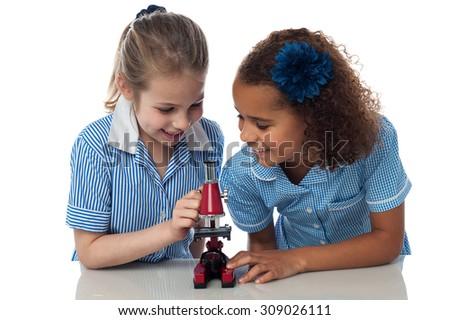 Little school girls working with microscope. - stock photo