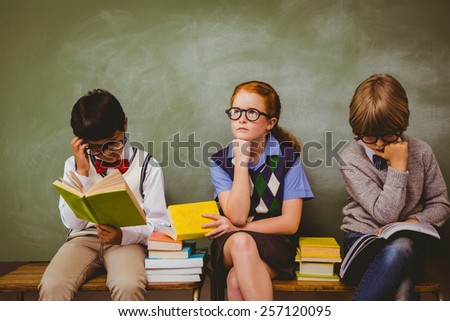 Little school kids with stack of books in classroom - stock photo