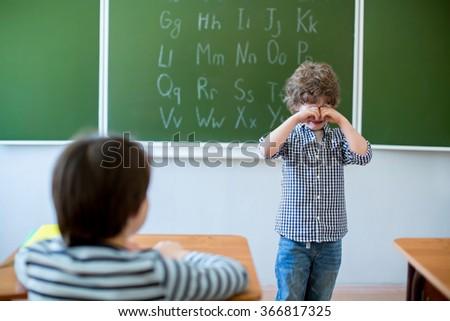 Little schoolboy crying at blackboard - stock photo
