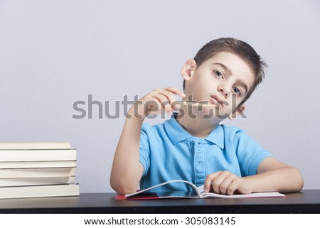 Little schoolboy having trouble with his homework - stock photo