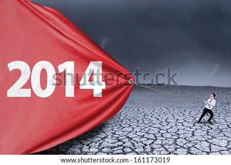 Little schoolboy is pulling banner of new year 2014 - stock photo