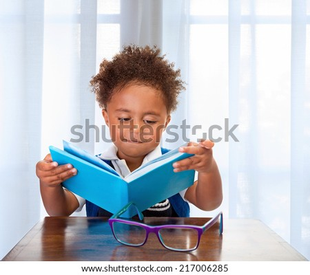 Little schoolboy read book in classroom, adorable african child learning lesson, doing homework, back to school concept - stock photo