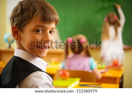 Little schoolboy  sitting behind school desk during lesson in school - stock photo