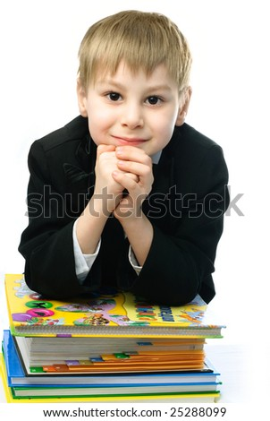little schoolboy sitting by the table with a lot of books standing on it - stock photo