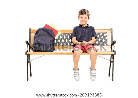 Little schoolboy sitting on a bench with a backpack isolated on white background - stock photo