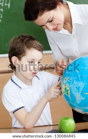 Little schoolboy studies geography - stock photo