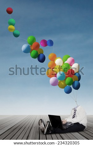 Little schoolboy with balloon head sitting on the wooden floor while using laptop computer - stock photo