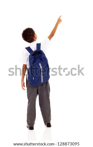 little schoolboy with schoolbag pointing at empty copy space - stock photo