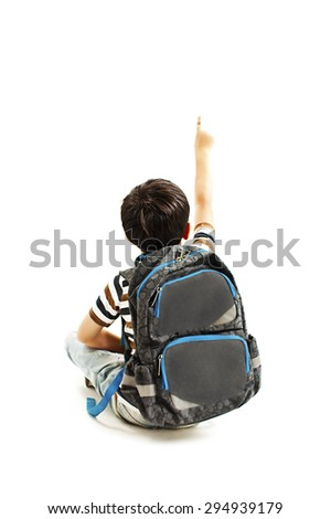 Little schoolboy with schoolbag pointing at empty copy space. Isolated on a white background - stock photo
