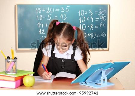 little schoolchild in classroom near blackboard - stock photo