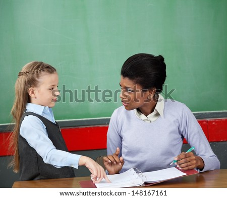 Little schoolgirl and female teacher looking at each other at desk in classroom - stock photo