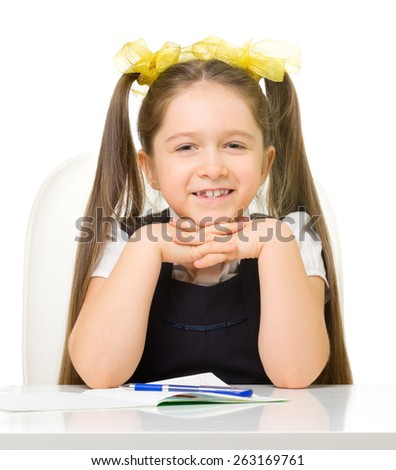 Little schoolgirl at the table isolated - stock photo