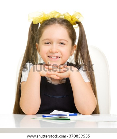 Little schoolgirl at the table isolated