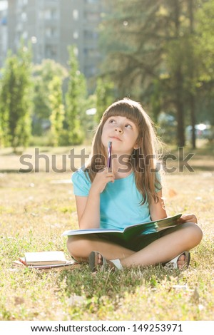 Little schoolgirl doing her homework in the park,Schoolgirl